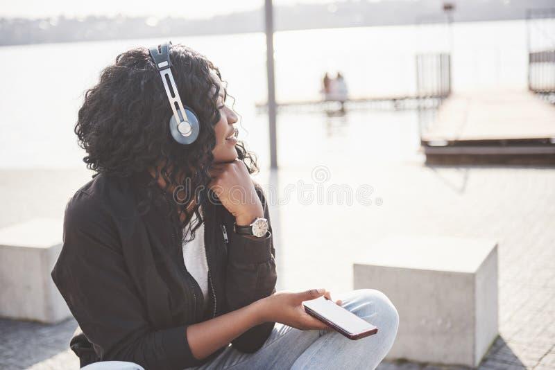 Stående av en härlig ung nätt afrikansk amerikanflicka som sitter på stranden eller sjön och lyssnar till musik i henne arkivbilder
