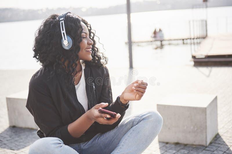 Stående av en härlig ung nätt afrikansk amerikanflicka som sitter på stranden eller sjön och lyssnar till musik i henne arkivfoto