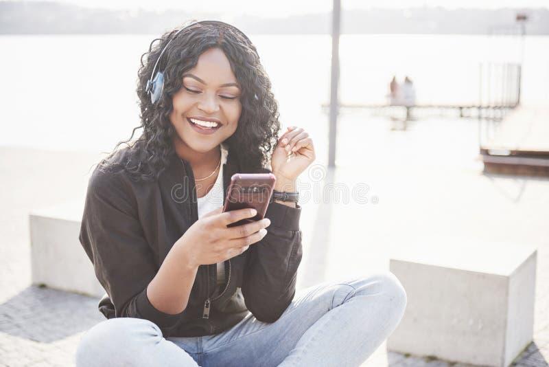 Stående av en härlig ung nätt afrikansk amerikanflicka som sitter på stranden eller sjön och lyssnar till musik i henne arkivfoton