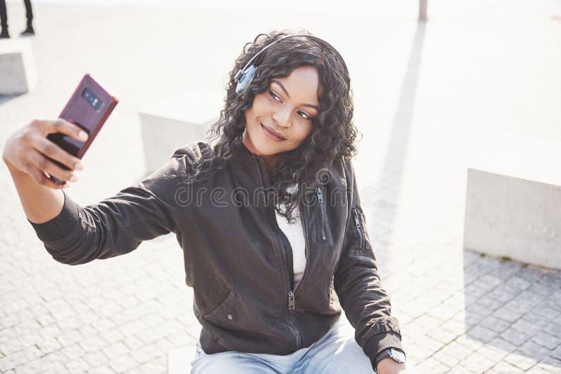 Stående av en härlig ung nätt afrikansk amerikanflicka som sitter på stranden eller sjön och lyssnar till musik i henne fotografering för bildbyråer