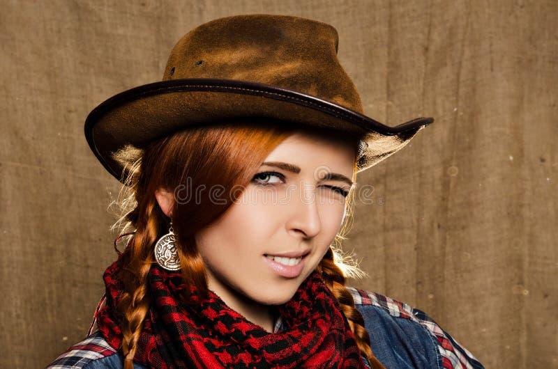 Stående av en härlig ung rödhårig flicka i en cowboyhatt royaltyfri bild