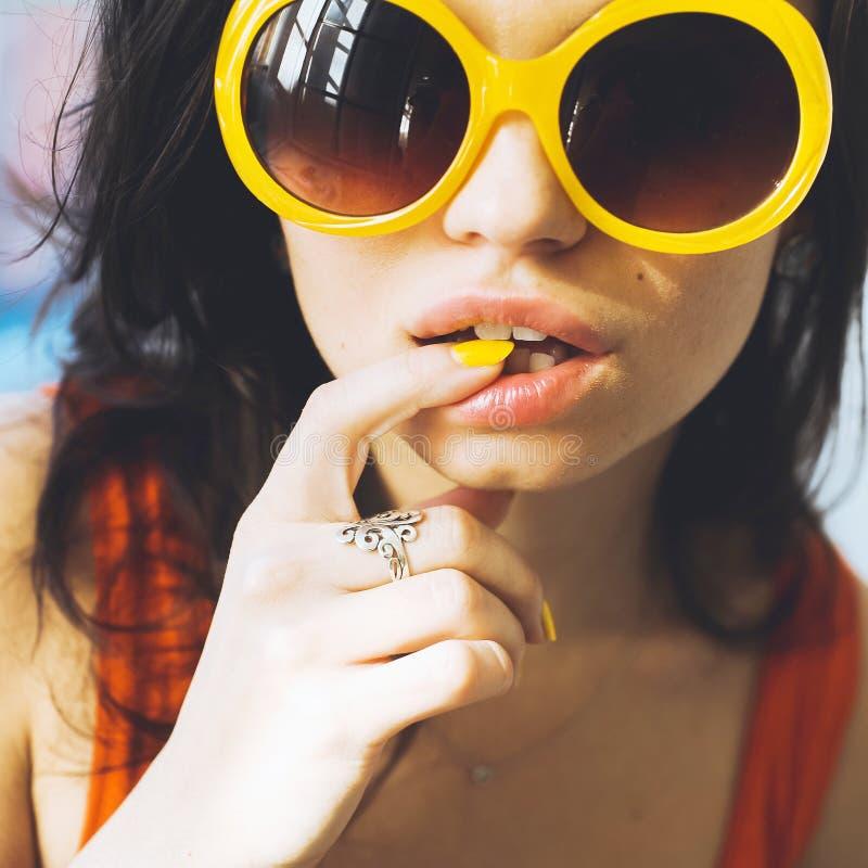 Stående av en härlig ung sexig brunettflicka med uttrycksfulla ögon och fulla kanter och solglasögon som poserar för kameran arkivbild