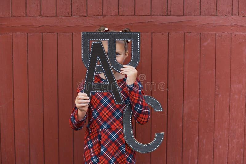 Stående av en härlig ung skolflicka på abc:et för bokstäver för röd träbakgrundswitn det stora Avsked Klocka Dag av kunskap royaltyfria foton
