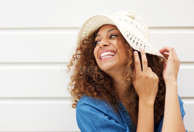 Stående av en härlig ung skratta och bärande sommarhatt för kvinna royaltyfri foto