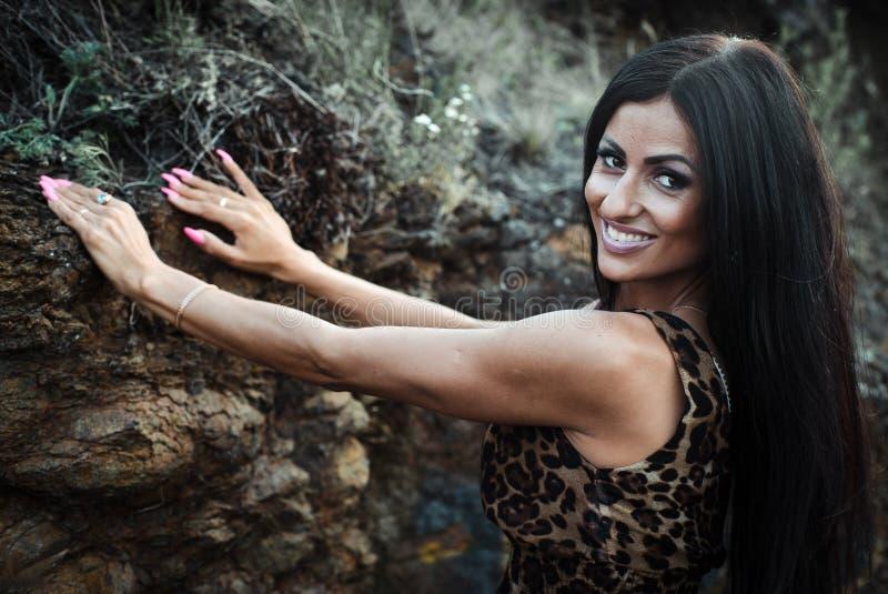 Stående av en härlig ung svart flicka i en leopardklänning royaltyfria foton