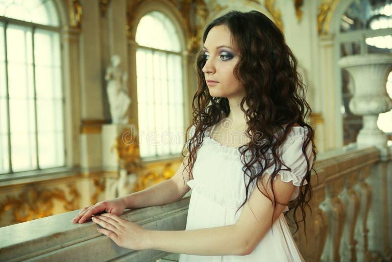 Stående av en härlig ung victorianlady i den vita klänningen arkivfoton