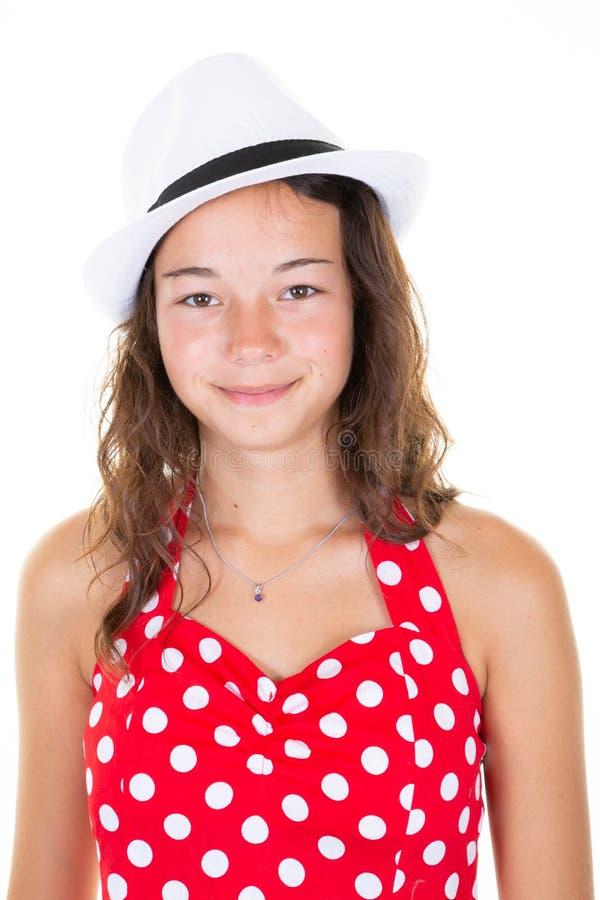 Stående av en härlig vit röd klänning- och hatttonåringflicka på en ljus bakgrund arkivbild
