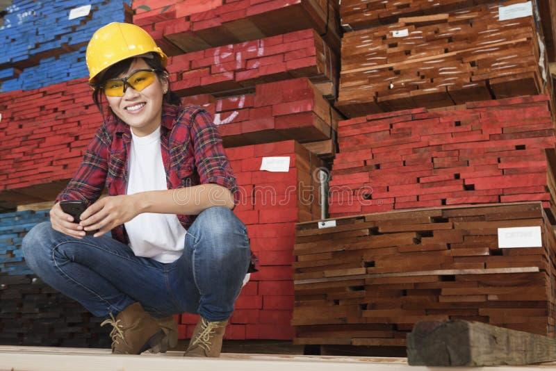 Stående av en hållande mobiltelefon för asiatisk kvinnlig industriarbetare med staplade träplankor i bakgrund arkivfoton