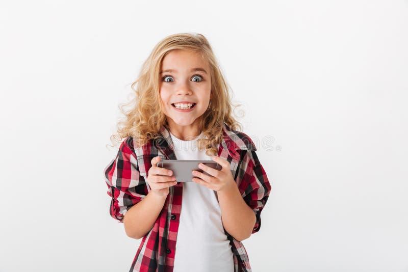 Stående av en hållande mobiltelefon för upphetsad liten flicka royaltyfria bilder