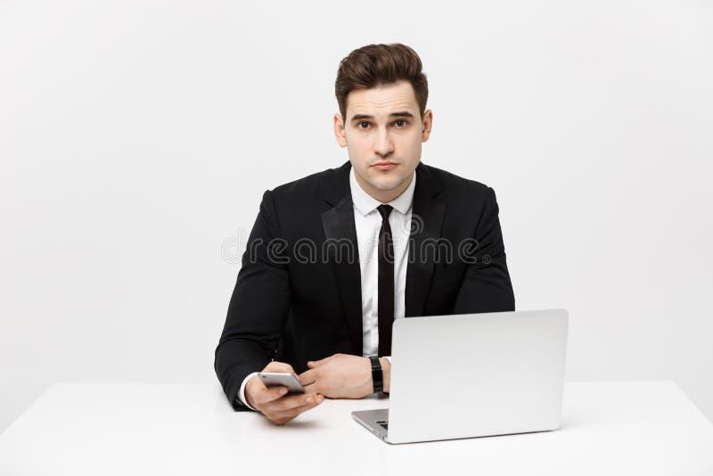 Stående av en hållande smartphone för stilig affärsman, medan arbeta på en dator på hans skrivbord Han är i ett hans kontor fotografering för bildbyråer