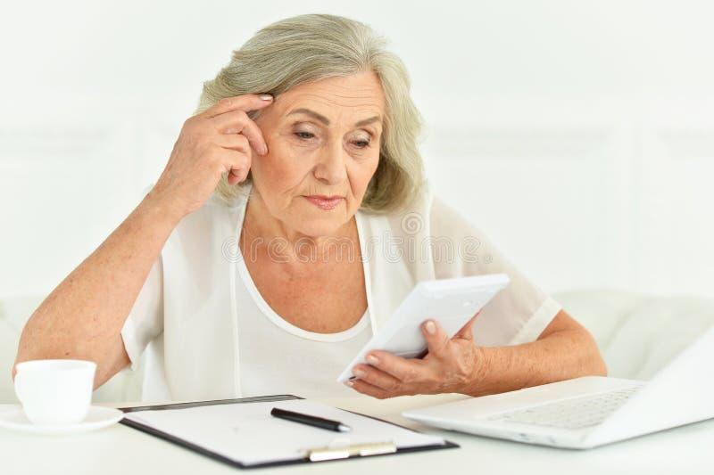 Stående av en hög affärskvinna med bärbara datorn arkivfoton