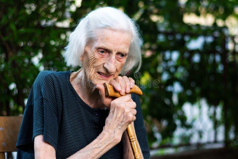 Stående av en hög kvinna med en gå rotting arkivfoto
