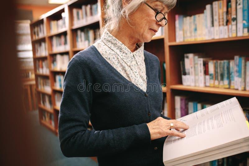 Stående av en hög kvinna som läser en bok i arkiv arkivfoto