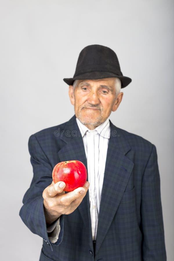 Stående av en hög man med hatten som erbjuder ett rött äpple royaltyfria foton