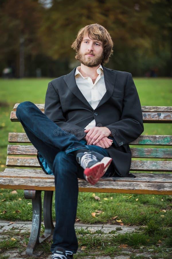 Stående av en hipsteraffärsman som sitter på en bänk royaltyfria bilder