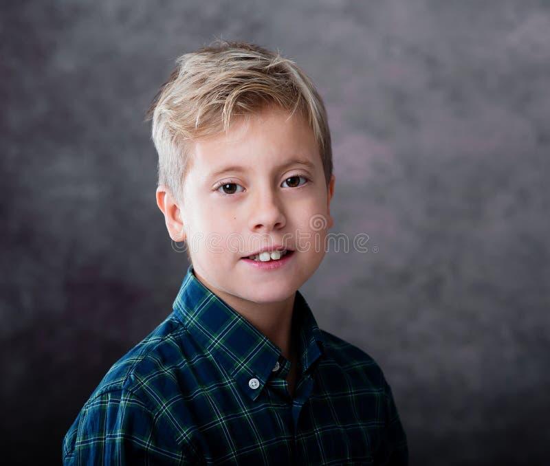 Stående av en iklädd gullig blond tonårs- pojke en plädskjorta arkivbilder