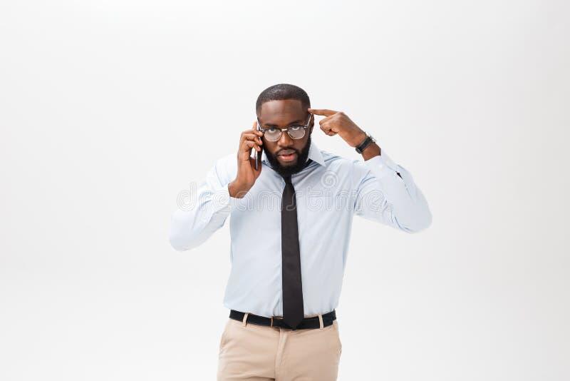 Stående av en iklädd vit skjorta för förvirrad ung afrikansk man som talar på mobiltelefonen och att göra en gest som över isoler royaltyfri foto