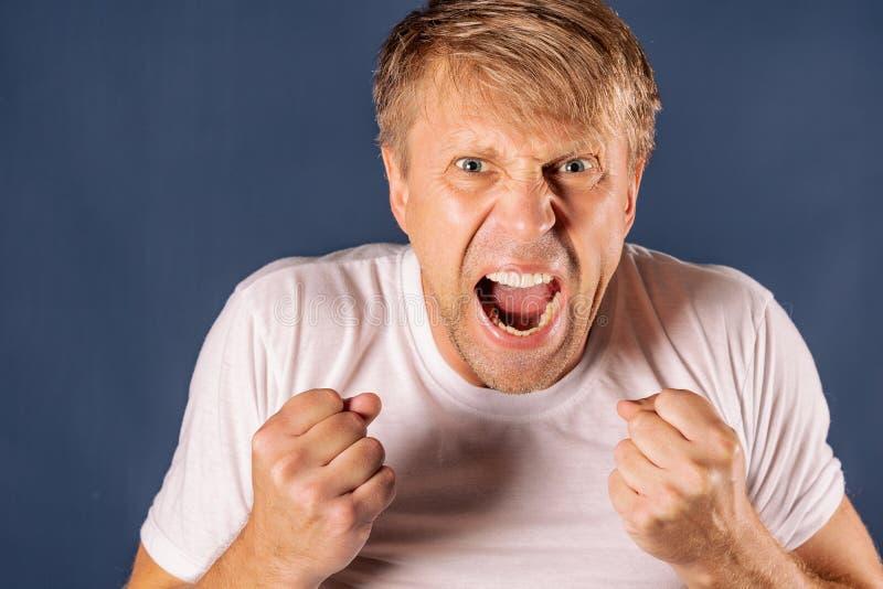 Stående av en ilsken man i den vita tshirten som rymmer nävar på blå bakgrund royaltyfri fotografi