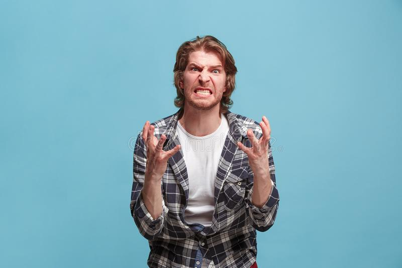 Stående av en ilsken man som ser kameran som isoleras på en blå bakgrund arkivbild