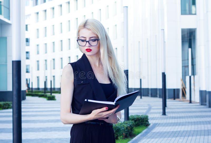 Stående av en intelligent kvinna som ser till den öppna anteckningsboken på bakgrunden av affärsmitten fotografering för bildbyråer