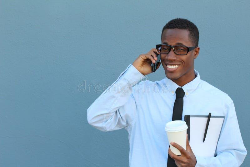 Stående av en kall ung afrikansk man i dräkt och bandet som går och talar på mobiltelefonen royaltyfri foto