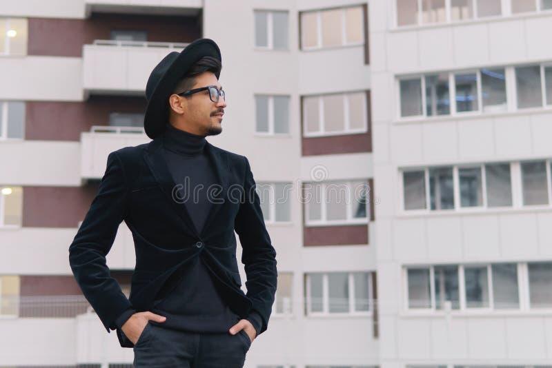 Stående av en kall ung man i svart dräkt och hatten som går på th arkivbild