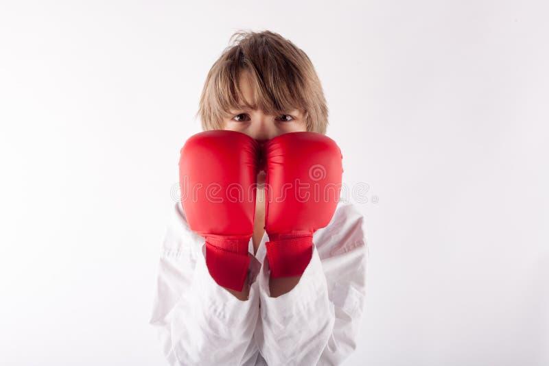 Stående av en karateunge som bär röda boxninghandskar royaltyfri foto