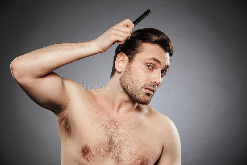 Stående av en koncentrerad shirtless man som kammar hans hår arkivfoto