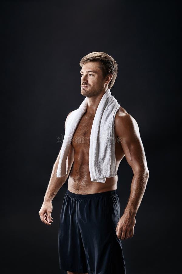 Stående av en konditionman med handduken på skuldror som bort ser Lycklig ung man som kopplar av, når utbildning arkivfoto