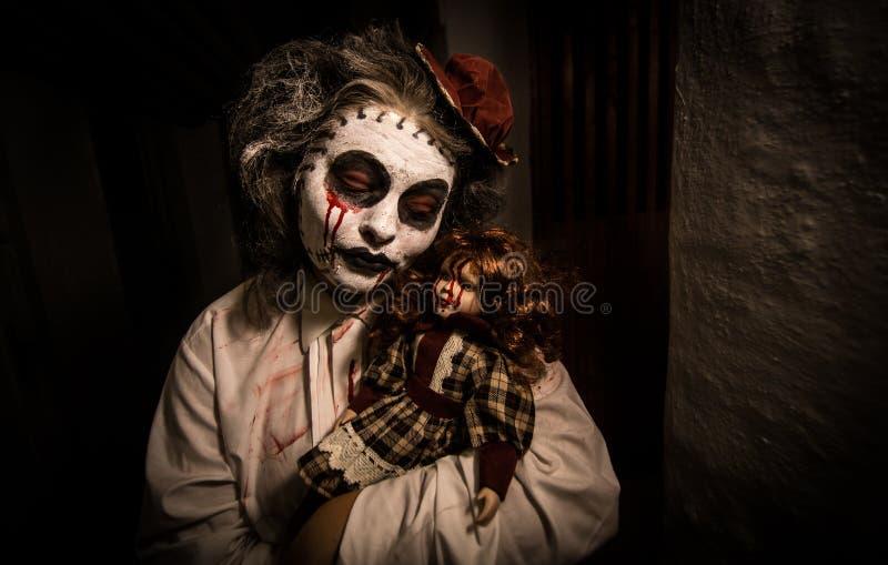 Stående av en kuslig flicka med den blodiga dockan arkivfoton