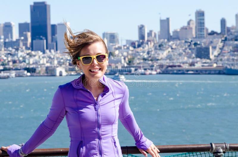 Stående av en kvinna framme av den San Francisco horisonten, som sett från vattnet i fjärden slågen hårwind arkivfoto