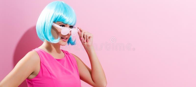 Stående av en kvinna i en ljus blå peruk royaltyfria foton