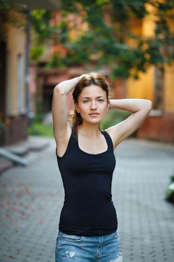 Stående av en kvinna i en svart T-tröja och jeans som står i arkivbilder
