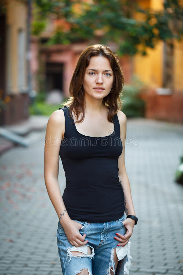 Stående av en kvinna i en svart T-tröja och jeans som står i arkivbild