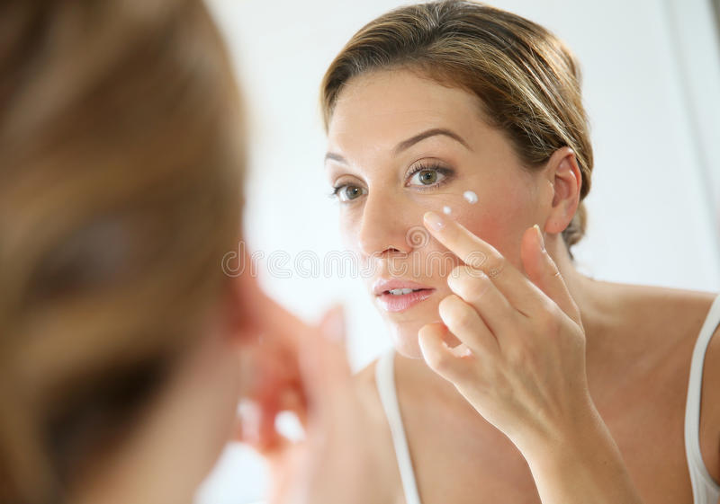 Stående av en kvinna i spegeln som applicerar en kräm royaltyfri foto
