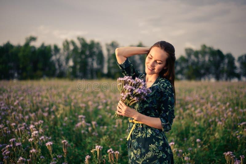 Stående av en kvinna med en bukett av lösa blommor i fältet på solnedgången royaltyfri foto