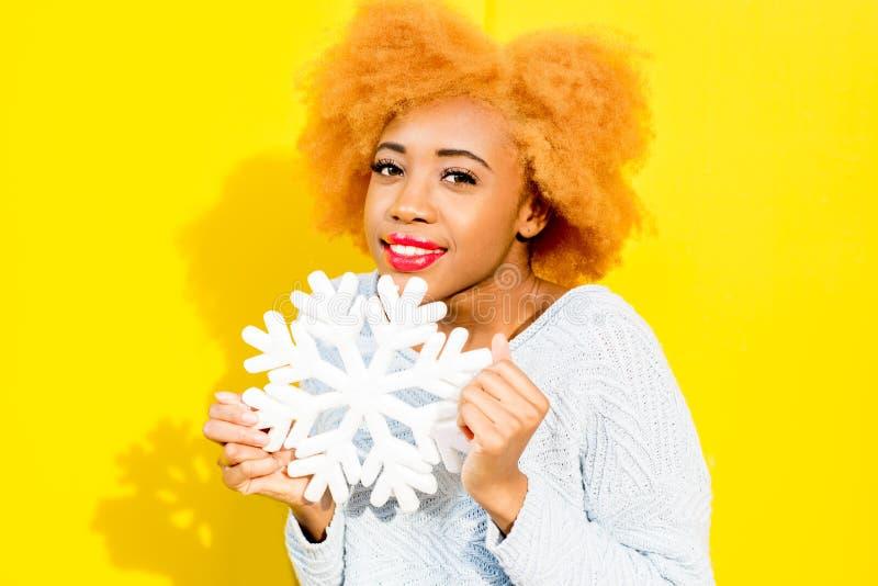 Stående av en kvinna med den konstgjorda snöflingan på den gula bakgrunden royaltyfri foto