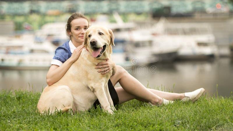 Stående av en kvinna med hennes härliga hund som utomhus ligger royaltyfri bild