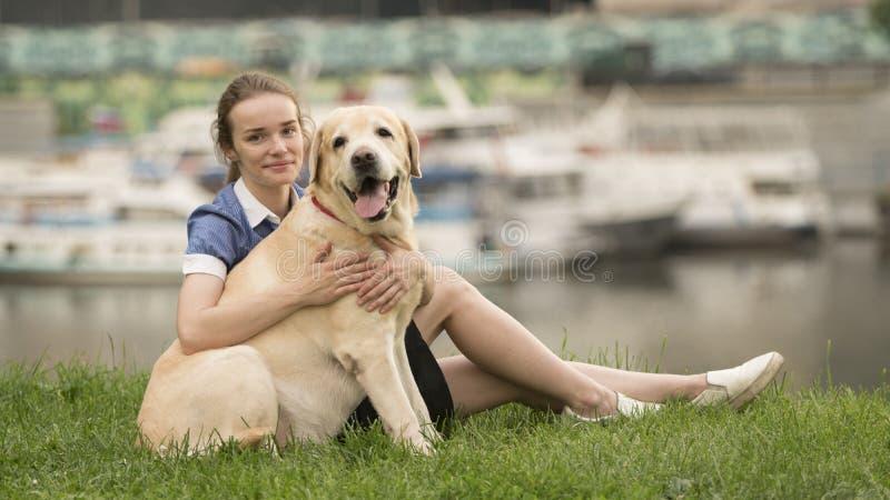 Stående av en kvinna med hennes härliga hund som utomhus ligger arkivfoto