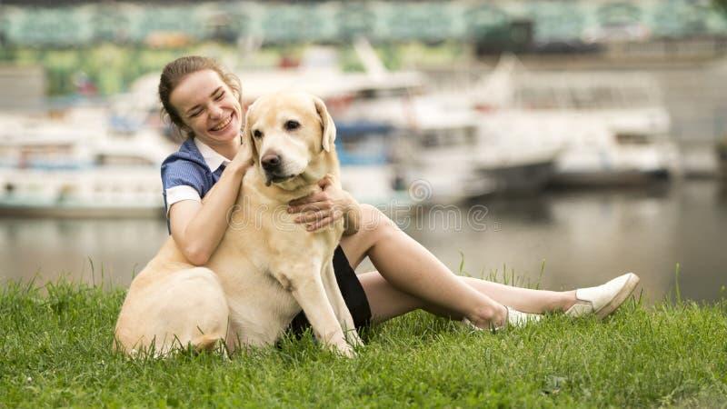 Stående av en kvinna med hennes härliga hund som utomhus ligger royaltyfri foto