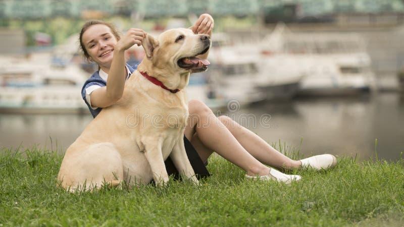 Stående av en kvinna med hennes härliga hund som utomhus ligger royaltyfri fotografi