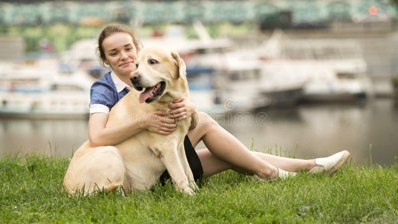 Stående av en kvinna med hennes härliga hund som utomhus ligger arkivbild