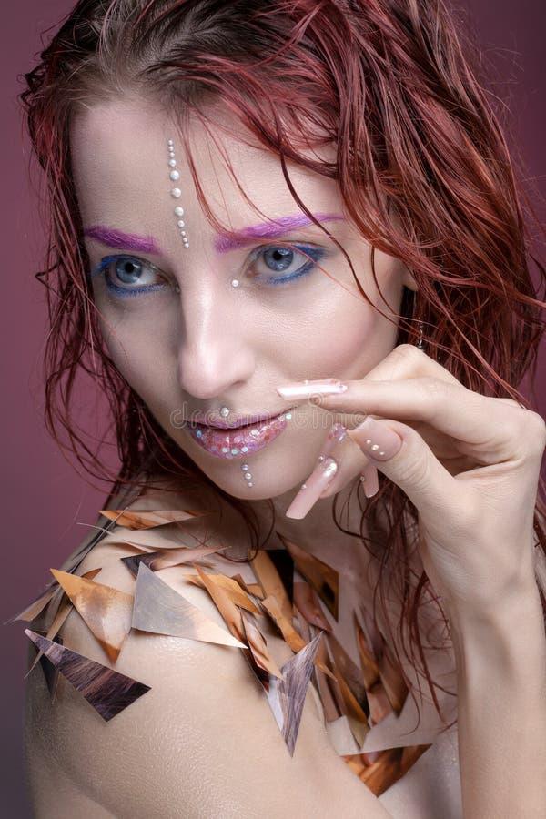 Stående av en kvinna med idérik makeup Med ljusa färger på arkivbild