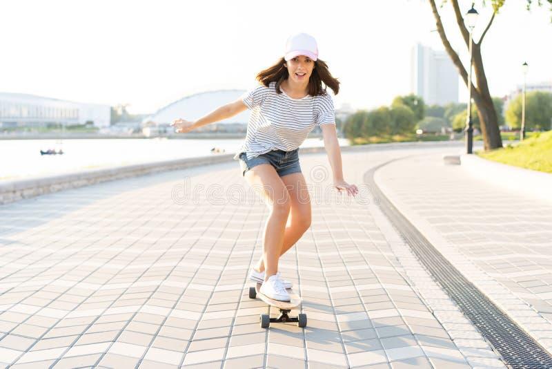 Stående av en kvinna med en skateboard på gatan, utomhus fotografering för bildbyråer