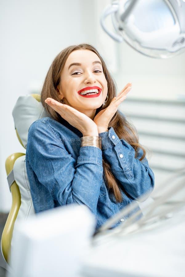 Stående av en kvinna med sunt leende i det tand- kontoret royaltyfri foto