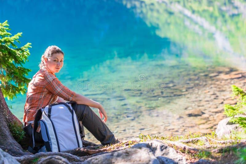 stående av en kvinna på en vandring som vilar nära en sjö i Tatraen M arkivbilder