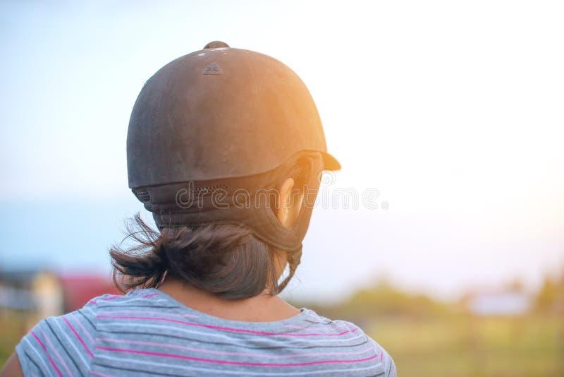 Stående av en kvinna som rider en häst, tillbaka sikt arkivfoto