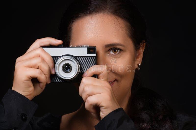Stående av en kvinna som tar fotoet på en retro kamera över svart bakgrund royaltyfri bild