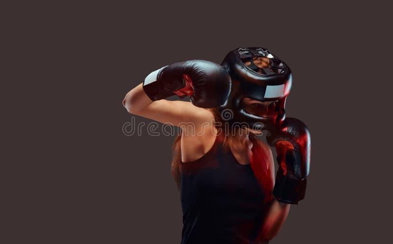 Stående av en kvinnlig boxare som bär den skyddande hjälmen och handskar under boxningövningar som fokuseras på process med allva arkivfoton