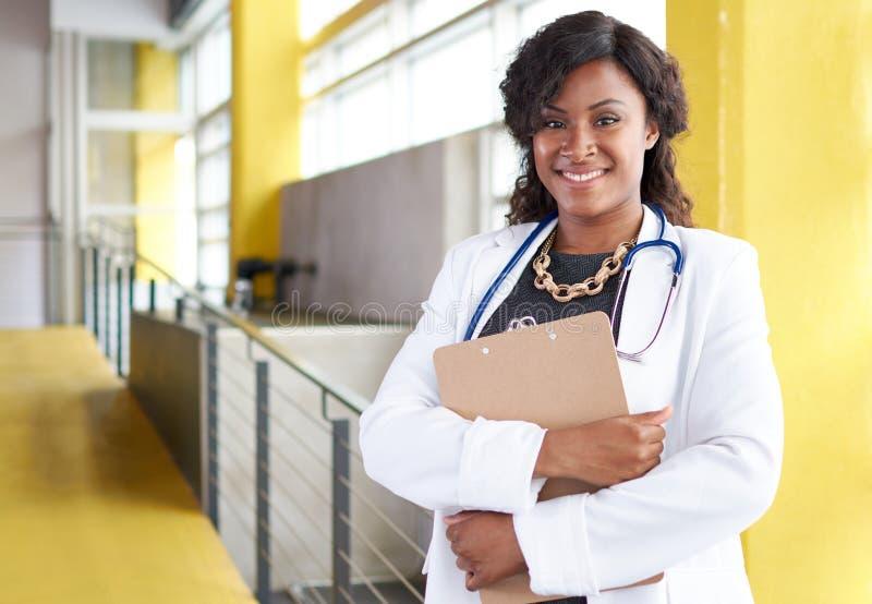 Stående av en kvinnlig doktor som rymmer hennes tålmodiga diagram i ljust modernt sjukhus arkivfoton